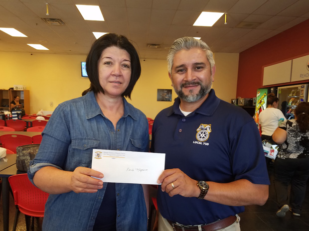 Teamsters Local 710 Business Agent Mike Ramirez (right) presents a scholarship award to Local 710 member Sandra Magana. Her daughter, Karla, won the scholarship based on her essay submission this summer.